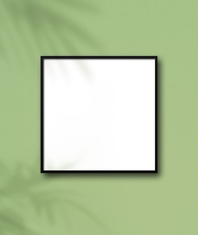 Black square picture frame hanging on a light green wall