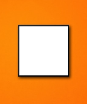 Black square picture frame hanging on an orange wall.