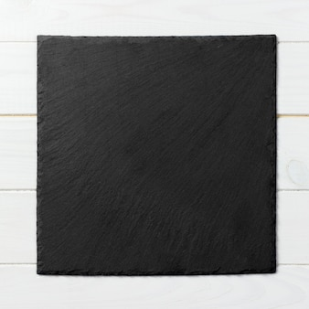 Black square plate on wooden background