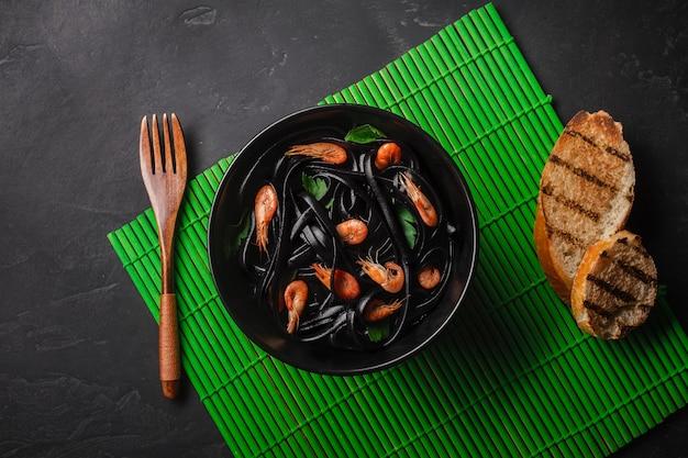 블랙 오징어 잉크 페투치니 파스타 새우 또는 새우, 파 슬 리, 와인 및 버터 소스에 칠리.