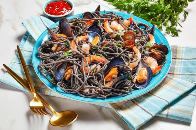 해산물을 곁들인 검은 오징어 먹물 파스타:케첩과 파슬리를 곁들인 흰색 대리석 배경에 황금 칼붙이가 있는 파란색 접시에 백포도주와 마늘 소스를 곁들인 홍합과 새우, 위쪽 전망, 클로즈업