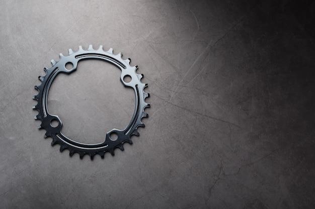 ナローワイド自転車コネクティングロッドシステムのブラックスター。黒の背景に走っている自転車の星の歯のパターン。ダークキーマクロ