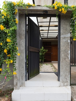 Black stell door fence entrance to home with cement block and white stones walkway