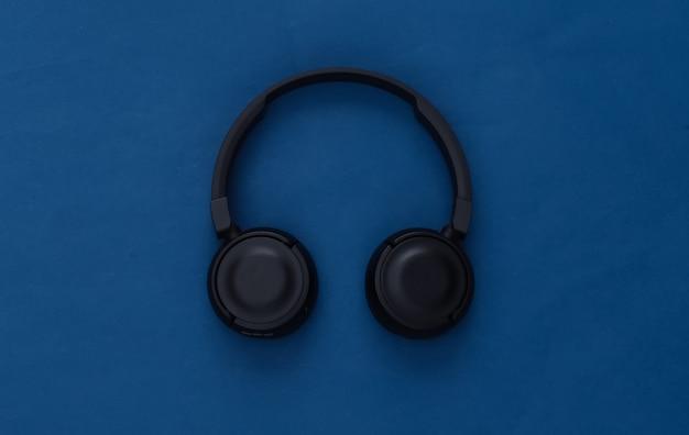 Black stereo headphones on classic blue