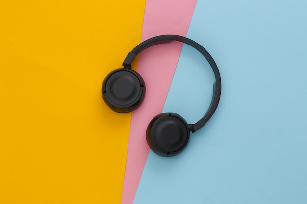 Black stereo headphones on colored table