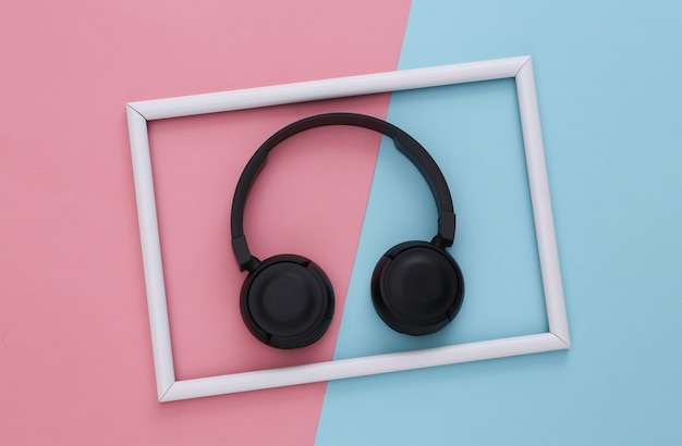 Black stereo headphones on a pink-blue with a white frame.