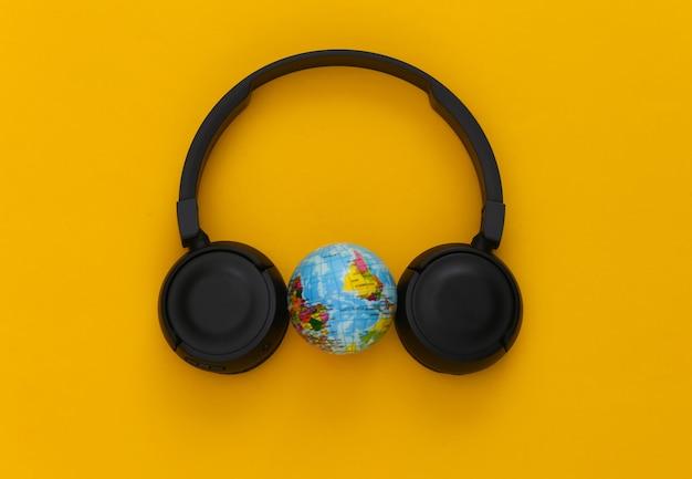 黄色に地球儀が付いた黒いステレオヘッドフォン。世界音楽の日