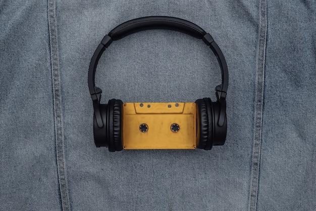 ブルージーンズの背景にオーディオカセット付きの黒のステレオヘッドフォン。