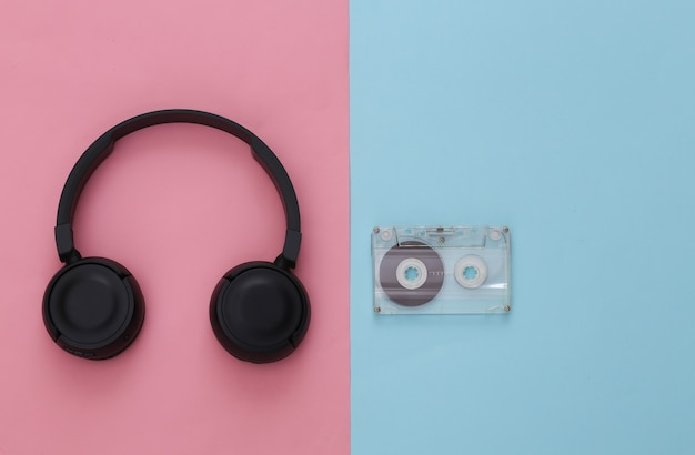 Black stereo headphones with retro audio cassette on pink blue pastel