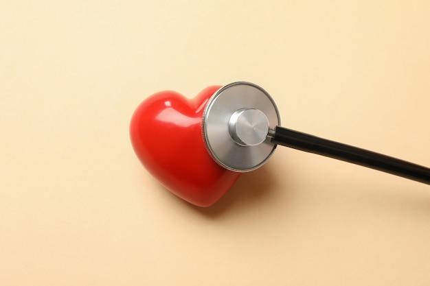 베이지 색 표면에 검은 청진 기 및 심장