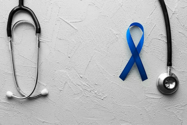 Black stethoscope and blue ribbon on plaster