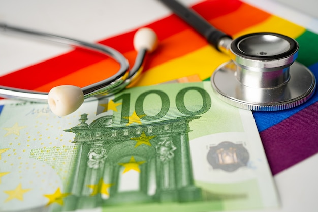 Black stethoscope and eu banknotes money on rainbow flag, symbol of lgbt pride month  celebrate annual in june social, symbol of gay, lesbian, bisexual, transgender, human rights and peace.