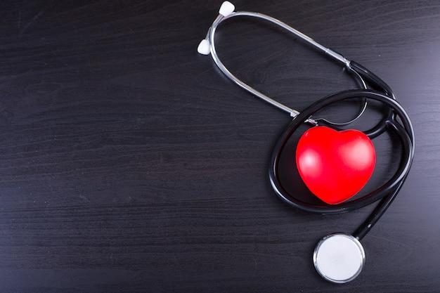 Сердце черного стетоскопа на черной деревянной доске.