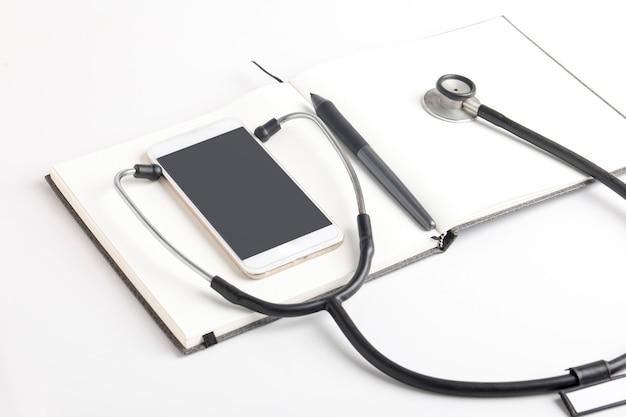 Black stethoscope lying on a blank notebook on white background