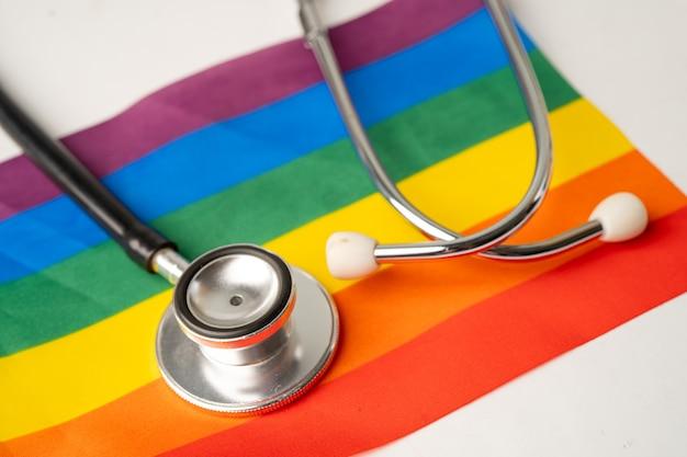 Черный стетоскоп на радужном флаге, символе месяца гордости лгбт