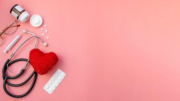 ピンクの検査のための赤い心臓と医者の薬の錠剤が付いている黒い聴診器
