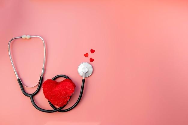 ピンクの検査のための医者の赤い心臓と黒い聴診器