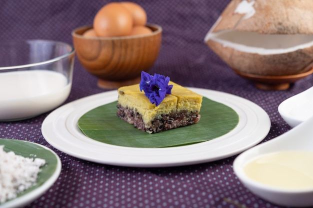 Black sticky rice and custard on a banana leaf in a white plate with butterfly pea flowers.