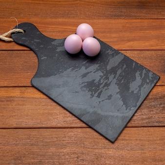 Черная каменная доска с пасхальными яйцами с пространством для текста