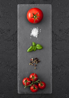 Black stone board with tomatoes, salt and pepper and basil on black table.