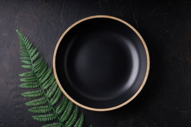 Black stone bowl with palm leaves on a black copy space dark photo mockup