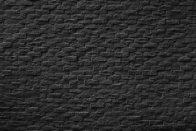 暗い背景のデザインの黒い石レンガの壁のテクスチャ。