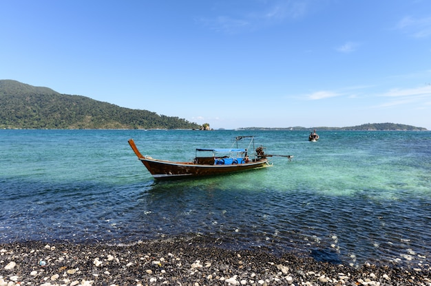 Black stone island with wooden boat on coastline in tropical sea