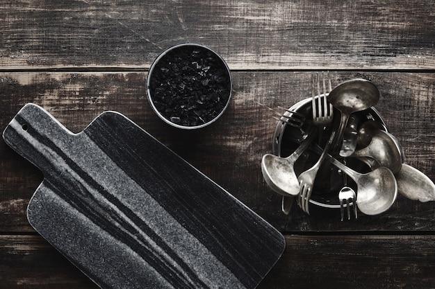 黒い石の大理石のカッティングデスク、バルカノソルト、ヴィンテージのキッチン用品:フォーク、ナイフ、熟成した木製のテーブルの上のスチールポットのスプーン。上面図。