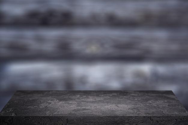 회색 나무 배경에 검은 돌 표면