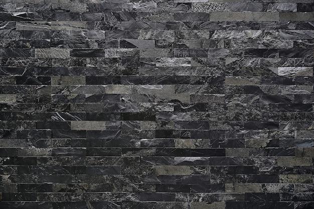 Черная каменная стена текстуры с квадратными кирпичными камнями