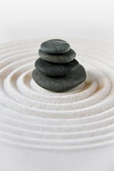砂の中に黒い石が積もっています。禅の日本庭園のシーン