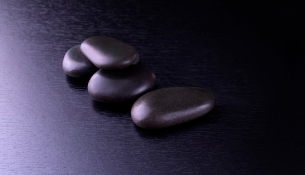 Black stones for thai spa on black wooden background