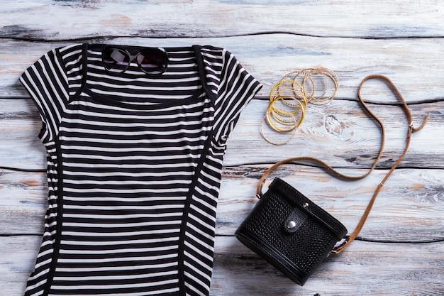 블랙 스트라이프 드레스와 선글라스. 캐주얼 드레스와 클래식 핸드백. 소녀의 어두운 봄 의상. 새 옷 할인.