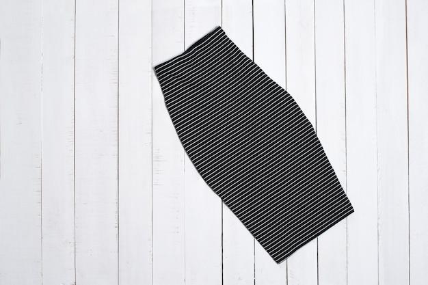 Черная полосатая юбка на белом фоне деревянных. концепция моды.