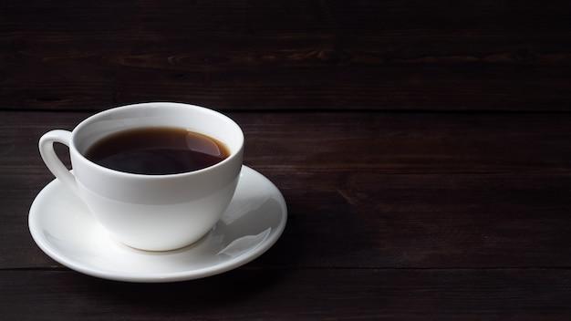 白いセラミックカップに入った黒い濃いエスプレッソコーヒー。木製の暗い背景、コピースペース。