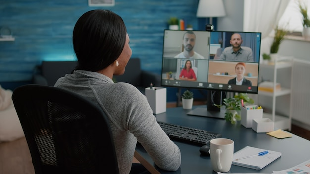 Black student discussing marketing academic ideas with college team having virtual teleconference meeting sitting at desk in living room