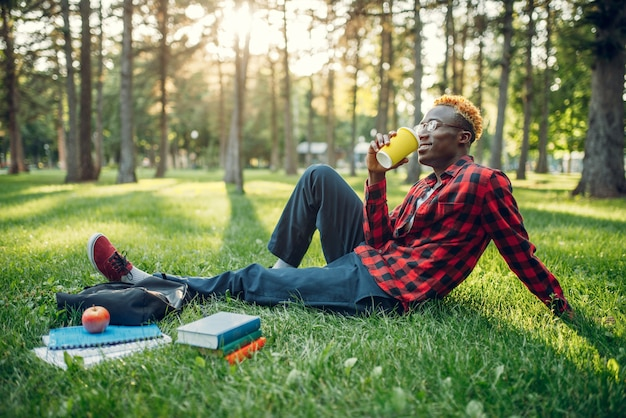Black student drinks coffee on the grass in park