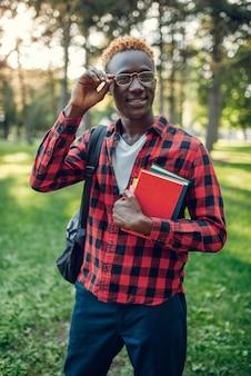 眼鏡をかけた黒人学生がサマーパークで本を持っています。屋外の芝生で勉強しているティーンエイジャー