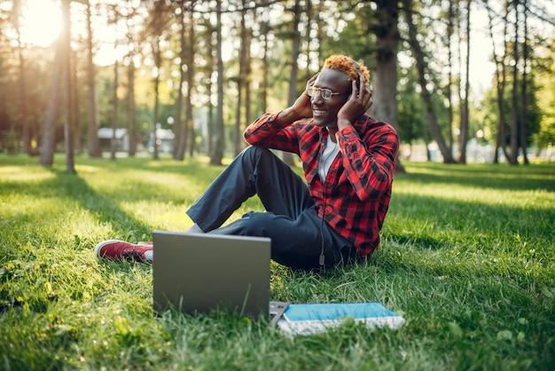 草の上に座っているヘッドフォンで黒人学生