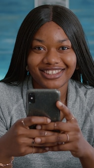Black student looking into camera while browsing social media typing message socializing with friends on modern smartphone. young woman sitting at desk in living room sharing group conversation