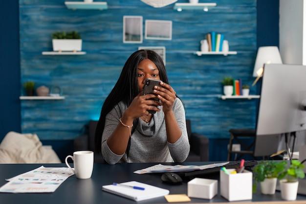 現代のスマールでメッセージを入力している友人グループと交流しながらカメラを見ている黒人学生...