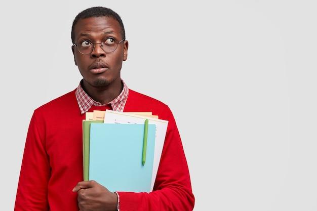 Studente nero guarda in alto con espressione pensierosa, porta libri di testo, indossa occhiali per una buona visione