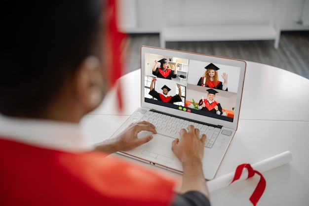 A black student sits at a laptop in a gown and square cap and communicates with fellow graduates virtual graduation and convocation ceremony laptop screen with happy students