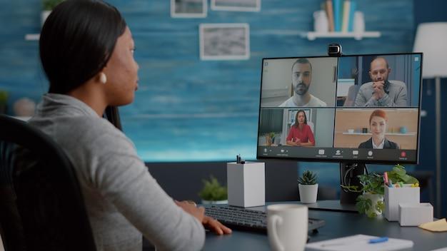 Темнокожий студент разговаривает с командой маркетингового университета во время видеоконференции онлайн, объясняя школьный виртуальный курс