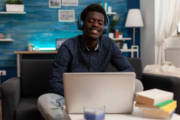 노트북에 오디오 비즈니스 코스가 있는 헤드폰을 끼고 있는 흑인 학생