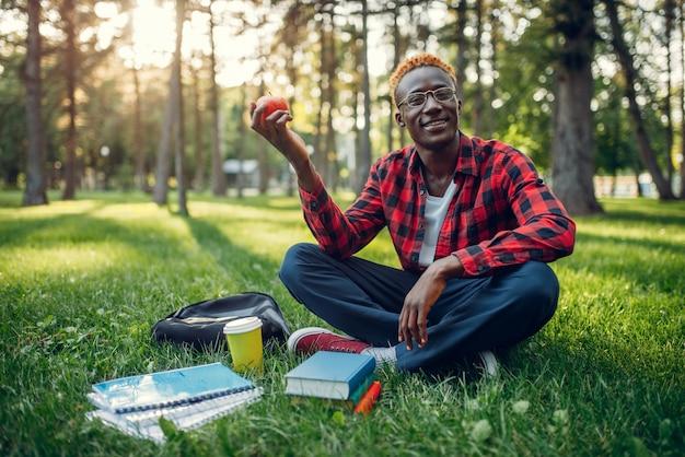 草の上に座っているリンゴと黒人学生