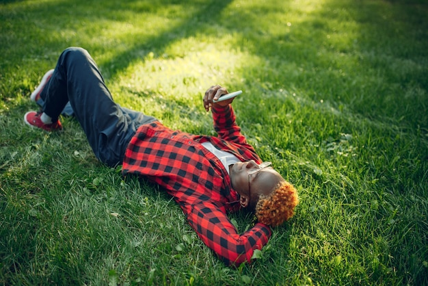 Black student with phone lying on the grass