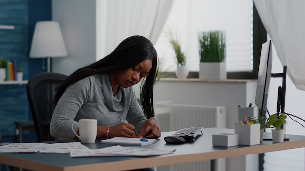 Black student writing education ideas on stickey notes sitting at desk table in living room
