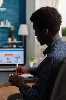 居間でラップトップコンピューターを使用してビジネスプレゼンテーションで働くノートブックに財務戦略を書いている黒人学生。コロナウイルスの封鎖中にオンライン学校を持っているティーンエイジャー