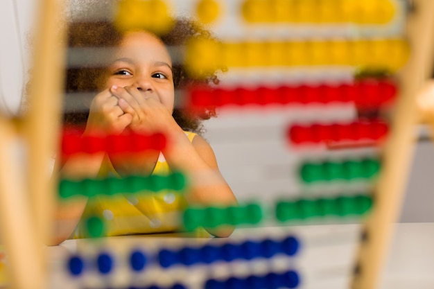 A black student in a yellow dress laughs brightly behind a colored abacus in an elementary school
